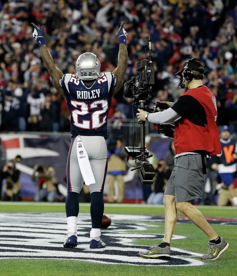 A cameraman follows as New England Patriots running back Stevan Ridley celebrates his eight-yard touchdown run during the second half of an AFC divisional playoff NFL football game against the Houston Texans in Foxborough, Mass., Sunday, Jan. 13, 2013. (AP Photo/Elise Amendola) Photo: Elise Amendola, Associated Press / AP