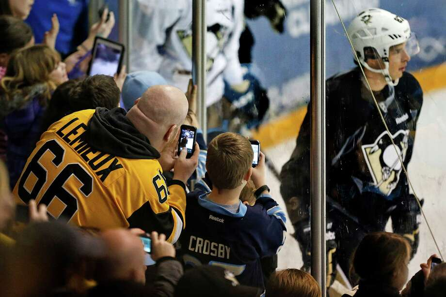 Penguins fans crowd along the boards to photograph Sidney Crosby during the team's first practice Sunday in Canonsburg, Pa. Photo: Gene J. Puskar, STF / AP
