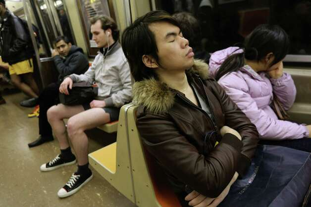 One subway passenger sleeps as others ride the train pantless on Sunday in New York City.  Photo: John Moore, Getty / 2013 Getty Images