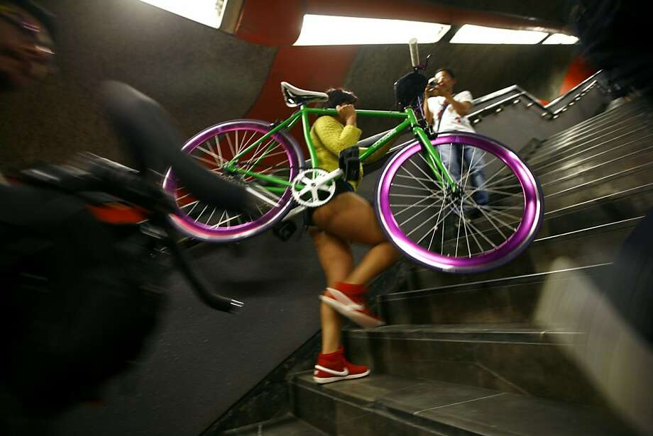 "Carrying a bike, a participant in the annual ""No Pants Subway Ride"" transfers to another train in Mexico City, Sunday, Jan. 13, 2013. (AP Photo/Marco Ugarte) Photo: Marco Ugarte, Associated Press"