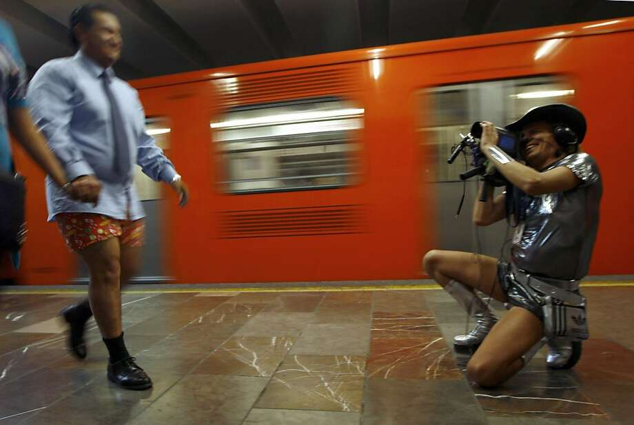 "A man, wearing underwear, records video of another man, also wearing underwear, during the annual ""No Pants Subway Ride"" at a subway station in Mexico City, Sunday, Jan. 13, 2013. (AP Photo/Marco Ugarte) Photo: Marco Ugarte, Associated Press"