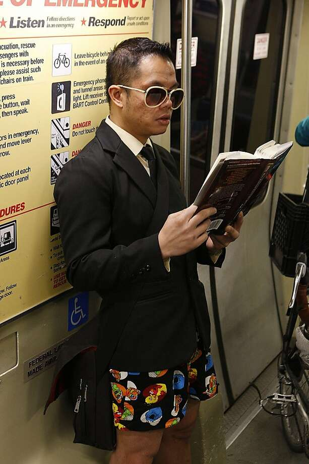 """No Pants"" participant Mark Calub, of San Francisco, reads a book while riding the BART in his underwear on January 13, 2013 in San Francisco, Calif. The event, which takes place in various subways around the world is hosted by the group Improv Everywhere, and asks participants to wear no pants but to don colorful underwear and socks Photo: Sean Havey, The Chronicle"