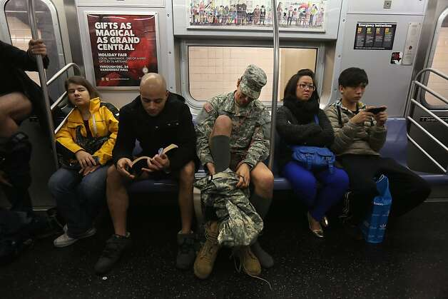 "NEW YORK, NY - JANUARY 13:  A soldier takes off his pants while riding the subway on January 13, 2013 in New York City. He and thousands of others participated in the 12th annual No Pants Subway Ride, organized by New York City prank collective Improv Everywhere. During the afternoon event, participants boarded separate subway stops and removed their pants, pretending that they did not know each other. The event, refered to as a ""celebration of silliness"" is designed to make fellow subway riders laugh and smile. (Photo by John Moore/Getty Images) Photo: John Moore, Getty Images"