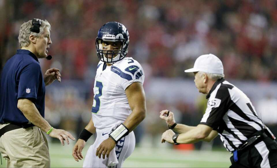 Seattle Seahawks head coach Pete Carroll talks to Russell Wilson during the first half of an NFC div