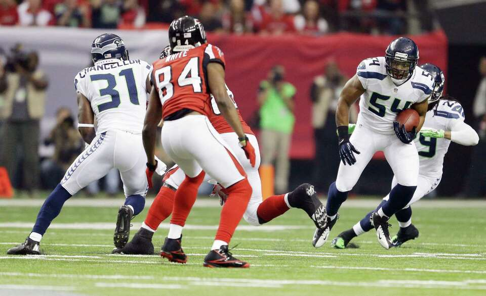 Seattle Seahawks' Bobby Wagner intercepts a pass during the first half of an NFC divisional playoff