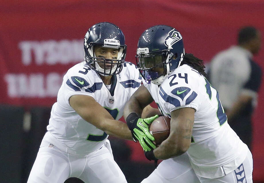 Seattle Seahawks' Russell Wilson hands off to Marshawn Lynch during the first half of an NFC divisional playoff NFL football game against the Atlanta Falcons Sunday, Jan. 13, 2013, in Atlanta. Photo: AP