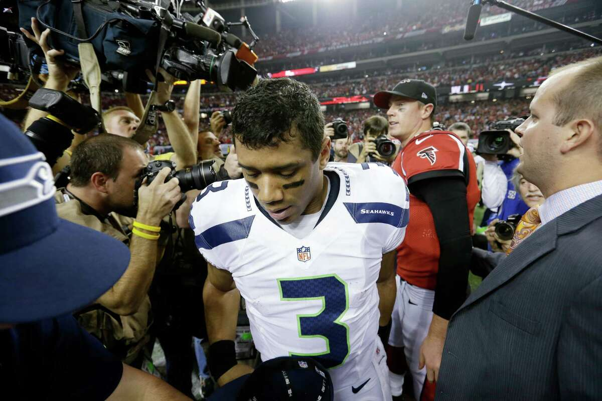 Matt Ryan (2) and Seattle Seahawks quarterback Russell Wilson leave the field during the second half of an NFC divisional playoff NFL football game Sunday, Jan. 13, 2013, in Atlanta. The Falcons won 30-28.