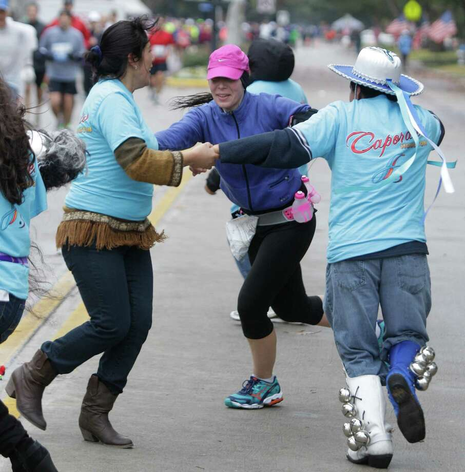 Bolivian dancers Janeth Flores, left, and Henry Patino, right, dance with runner Amanda McClure, center, along University near mile 13 of the Chevron Houston Marathon Sunday, Jan. 13, 2012 in West University. Photo: Melissa Phillip, Houston Chronicle / © 2013 Houston Chronicle