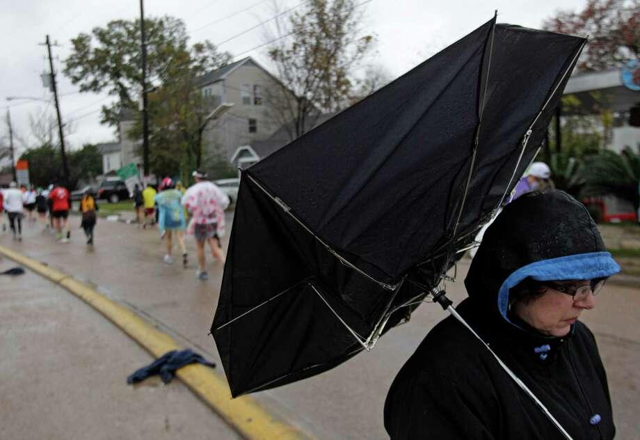 Phyllis Sabo of Houston waits in the rain to see her son, Ed Sabo, run past on Studewood near White Oak during the Chevron Houston Marathon and Aramco Houston Half Marathon Sunday, Jan. 13, 2013, in Houston. Photo: Melissa Phillip, Houston Chronicle / © 2013 Houston Chronicle