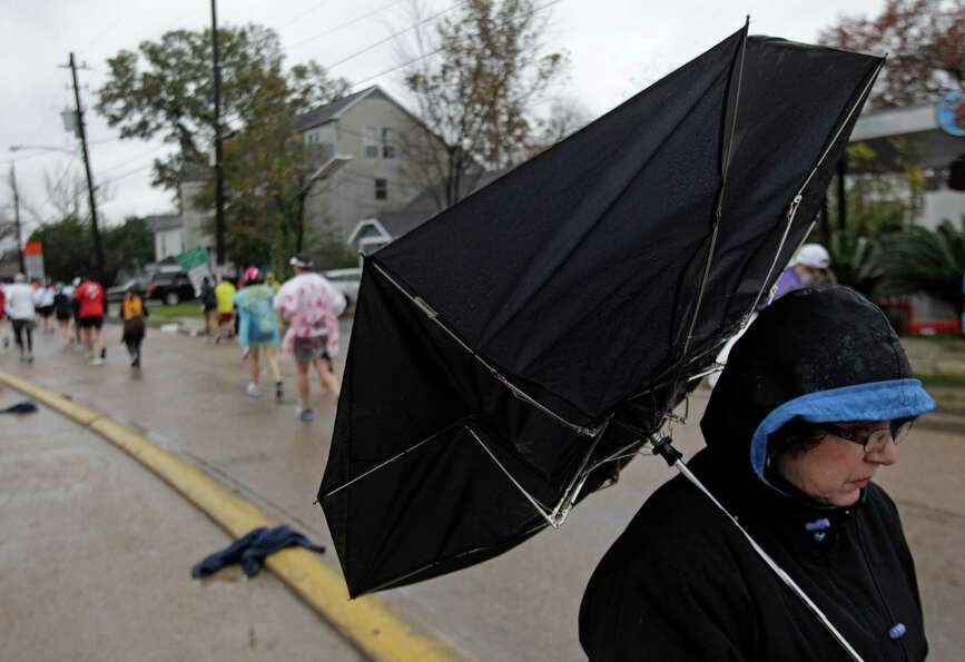 Phyllis Sabo of Houston waits in the rain to see her son, Ed Sabo, run past on Studewood near White