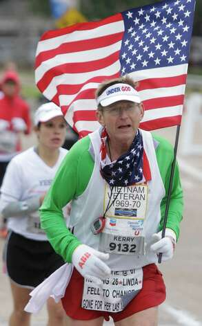 Kerry Walsh carries a US flag as he runs along Allen Parkway during the Chevron Houston Marathon Sunday, Jan. 13, 2012. Sunday, Jan. 13, 2013, in Houston. Photo: Melissa Phillip, Houston Chronicle / © 2013 Houston Chronicle
