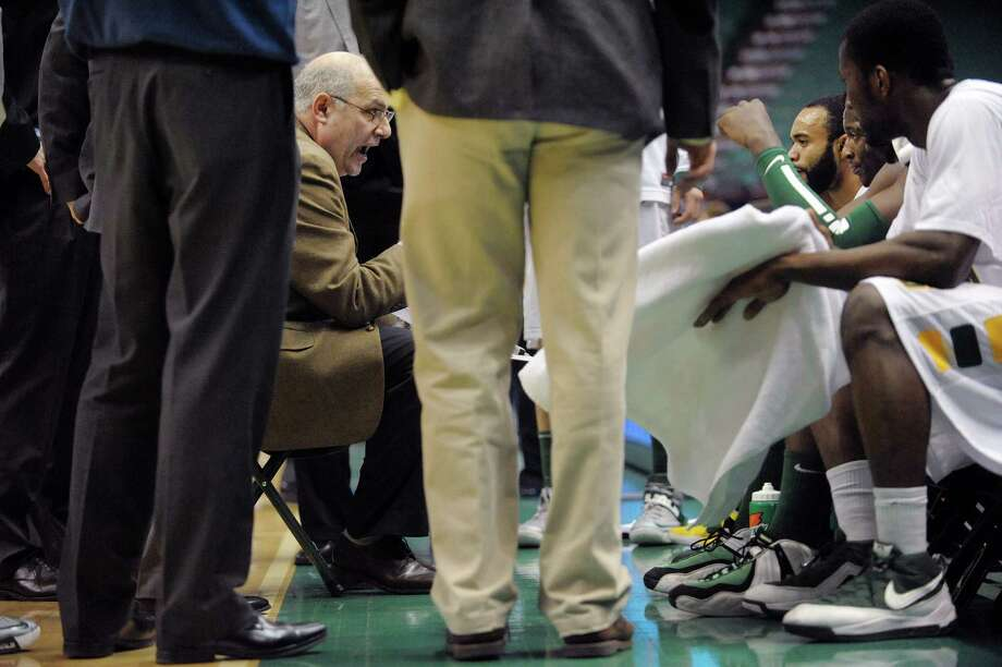 Siena's head coach Mitch Buonaguro, left, talks to his players duirng a time out in the second half during their game against Saint Peter's at the Times Union Center on Sunday, Jan. 13, 2013 in Albany, NY. (Paul Buckowski / Times Union) Photo: Paul Buckowski  / 00020599D
