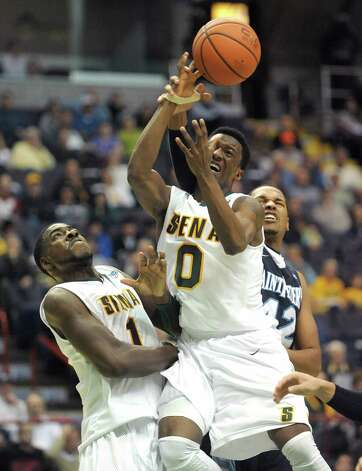 Siena's O.D. Anosike, left, and Rich Audu, center, battle Saint Peter's players for the ball during their game at the Times Union Center on Sunday, Jan. 13, 2013 in Albany, NY.  (Paul Buckowski / Times Union) Photo: Paul Buckowski  / 00020599D