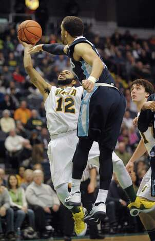 Siena's Rakeem Brookins, left, puts up a shot just out of the reach of a Saint Peter's player during their game at the Times Union Center on Sunday, Jan. 13, 2013 in Albany, NY.  (Paul Buckowski / Times Union) Photo: Paul Buckowski  / 00020599D