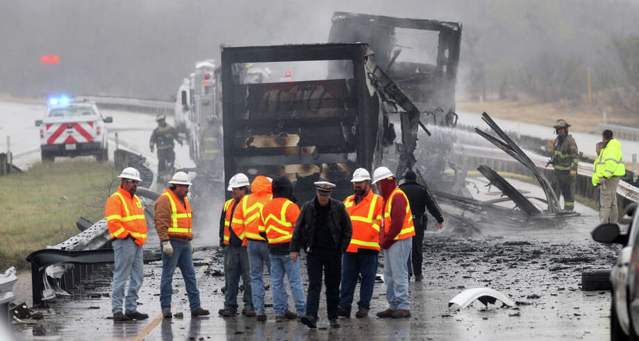 San Antonio police, fire and other personnel stand by the scene of a truck Tuesday January 8, 2013  that caught on fire after sideswiping a guardrail on a highway ramp connecting Loop 410 south to IH-37 south of downtown San Antonio. According to San Antonio police sergeant Donald Mize the truck was empty and the driver was not injured. No other vehicles were involved in the accident. Photo: JOHN DAVENPORT, San Antonio Express-News / ©San Antonio Express-News