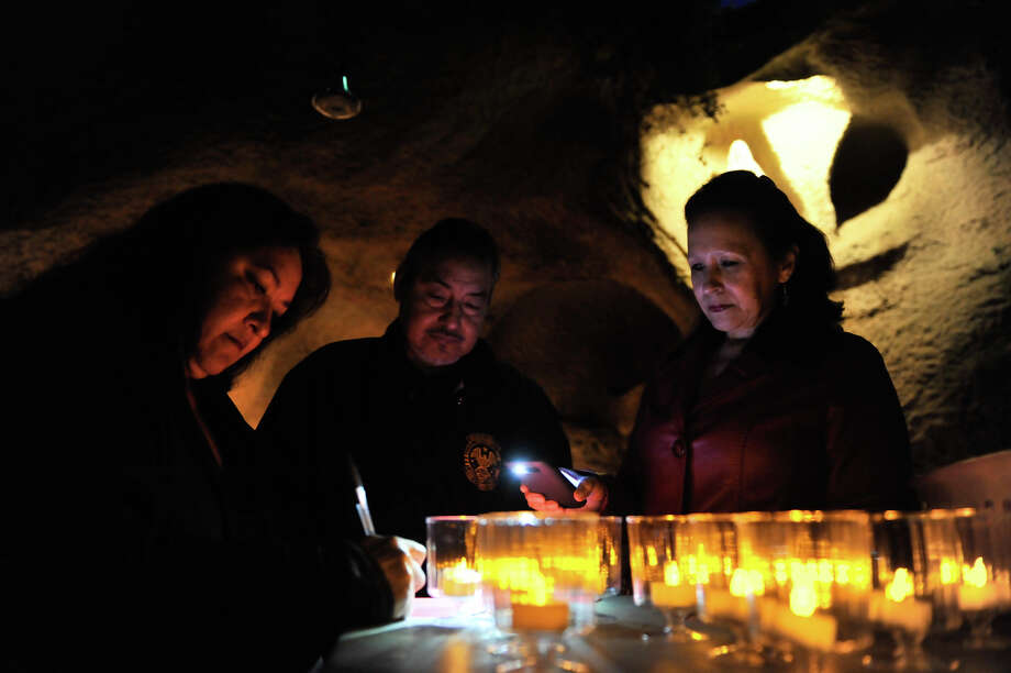 Betty Garza Mendoza (left) signs a card for the victims of the Newtown shootings as Philip Moreno and Patricia Doria turn on electric candles for the 26th night of prayer vigils at Our Lady of Lourdes Grotto Wednesday evening. Photo: Robin Jerstad