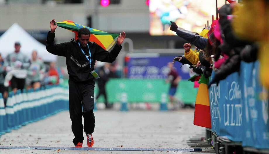 With an Ethiopian flag draped over his shoulders, Bazu Worku takes a victory lap after winning the men's crown in the Chevron Houston Marathon on Sunday. Worku's time of 2:10:17 was nearly three minutes better than countryman Teferi Balcha, who was second. Photo: James Nielsen, Staff / © Houston Chronicle 2013
