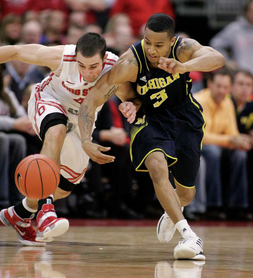Ohio State's Aaron Craft, left, and Michigan's Trey Burke vie for a loose ball Sunday as part of a spirited confrontation between the point guards that saw Craft hold Burke to 15 points on 4-for-13 shooting. Photo: MIKE MUNDEN, FRE / FR57028 AP