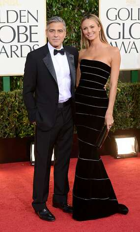 George Clooney wears a traditional tuxedo while actress Stacy Keibler goes strapless in an Armani gown on the red carpet at the 70th Golden Globe Awards. Photo: Jason Merritt, Getty Images