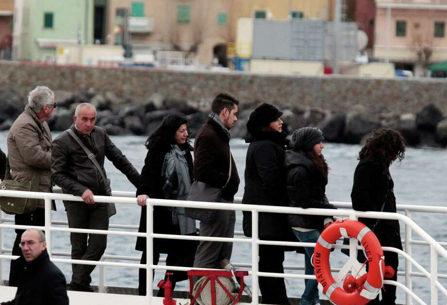 Relatives of the 32 victims of the Costa Concordia shipwreck, aboard a ferry approach the ship off the Tuscan Island Isola del Giglio, Italy, Sunday, Jan. 13, 2013. Survivors of the Costa Concordia shipwreck and relatives of the 32 people who died marked the first anniversary of the grounding Sunday. The first event of Sunday's daylong commemoration was the return to the sea of part of the massive rock that tore into the hull of the 112,000-ton ocean liner on Jan. 13, 2012 and remained embedded as the vessel capsized along with its 4,200 passengers and crew. (AP Photo/Gregorio Borgia) Photo: Gregorio Borgia