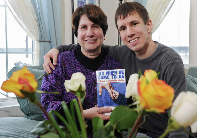 Ellie Parker and her son, Dmitry, 26, whom she adopted from Russia at age 6, sit on a couch at their home on Thursday Jan. 3, 2013 in Malta, N.Y. (Lori Van Buren / Times Union) Photo: Lori Van Buren