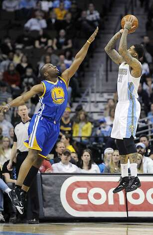 The Warriors' Carl Landry leaps to defend a first-quarter shot by Denver's Wilson Chandler, who had 14 points. Chandler was one of three Denver reserves with double-digit points. Photo: Chris Schneider, Associated Press