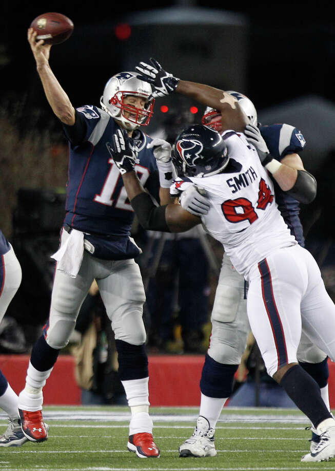 Patriots quarterback Tom Brady (12) throws a pass over Texans defensive end Antonio Smith (94) during the second quarter. Photo: Brett Coomer, Houston Chronicle / © 2013  Houston Chronicle