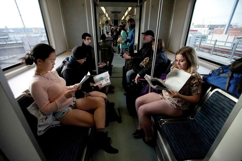 Participants, including Lu Zeng, left, read newspapers during Emerald City Improv's No Pants Light Rail Ride on Sunday, January 13, 2013. Dozens of participants took off their pants while riding on the train, shocking some other passengers. Photo: JOSHUA TRUJILLO, SEATTLEPI.COM / SEATTLEPI.COM