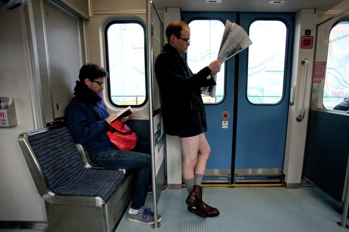 A participant reads the newspaper during Emerald City Improv's No Pants Light Rail Ride on Sunday, January 13, 2013. Dozens of participants took off their pants while riding on the train, shocking some other passengers.