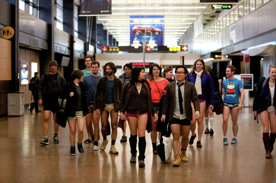 Participants walk through the airport during Emerald City Improv's No Pants Light Rail Ride on Sunda