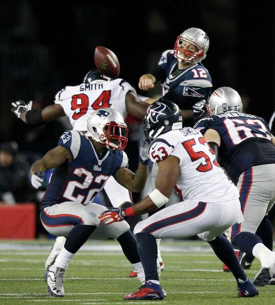 Patriots quarterback Tom Brady (12) tries to get off a pass as Houston Texans defensive end Antonio