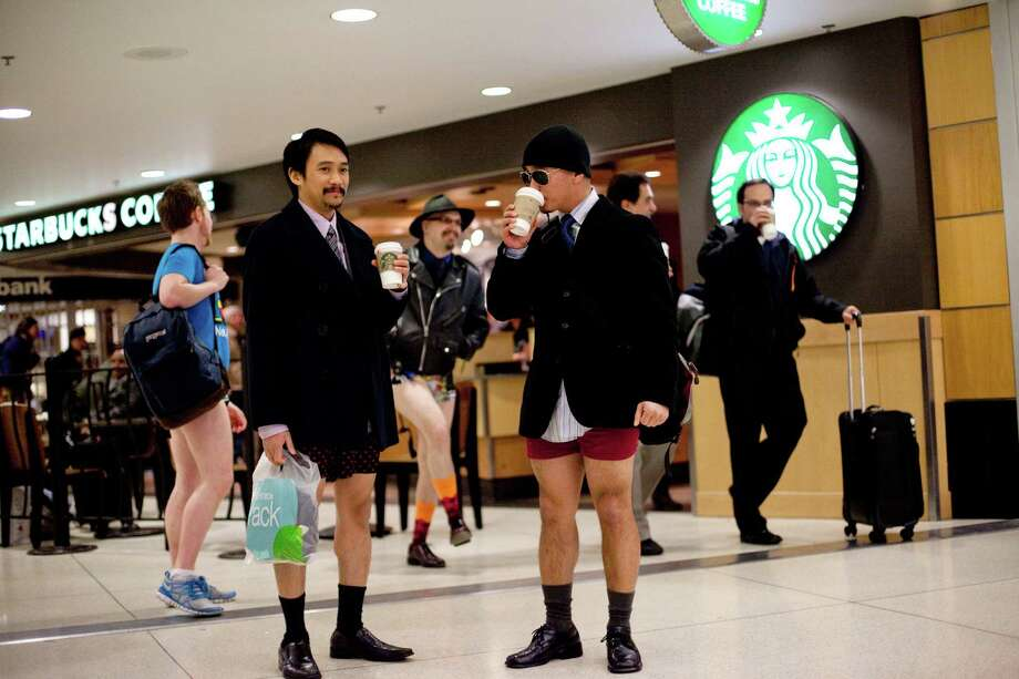 Participants sip coffee in Sea-Tac Airport during Emerald City Improv's No Pants Light Rail Ride on Sunday, January 13, 2013. Dozens of participants took off their pants while riding on the train, shocking some other passengers. Photo: JOSHUA TRUJILLO, SEATTLEPI.COM / SEATTLEPI.COM