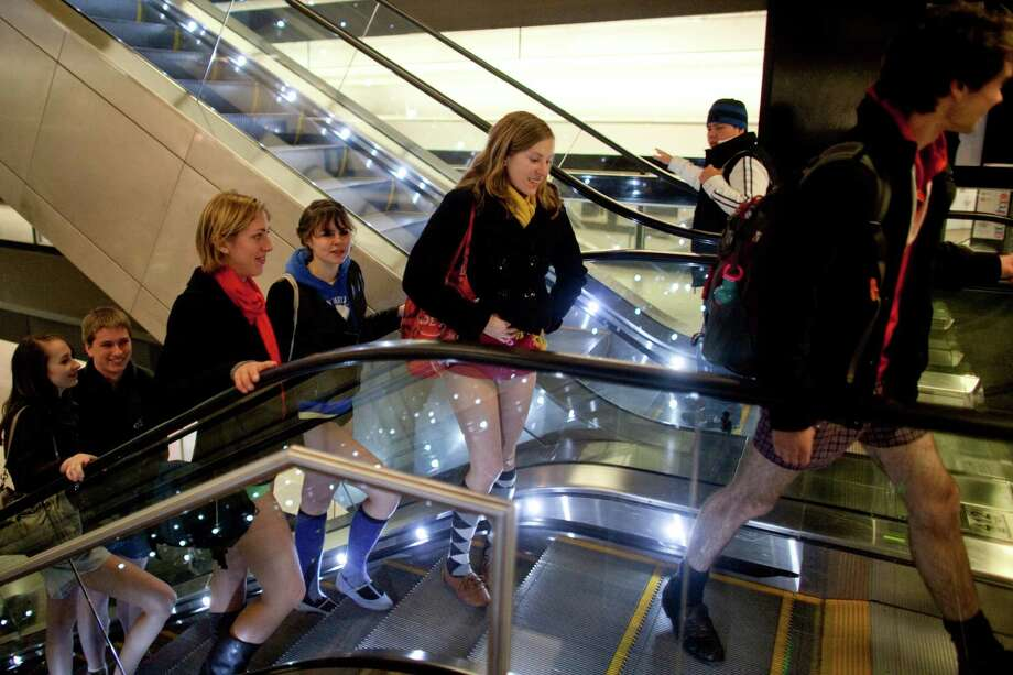 Participants ride the escalator at Sea-Tac Airport during Emerald City Improv's No Pants Light Rail Ride on Sunday, January 13, 2013. Dozens of participants took off their pants while riding on the train, shocking some other passengers. Photo: JOSHUA TRUJILLO, SEATTLEPI.COM / SEATTLEPI.COM