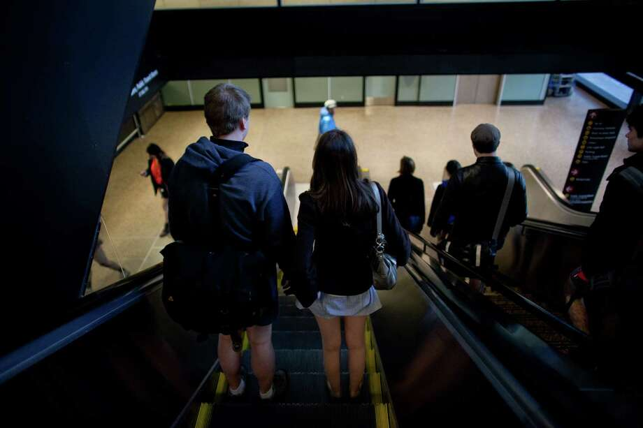 Participants ride an escalator in Sea-Tac Airport during Emerald City Improv's No Pants Light Rail Ride on Sunday, January 13, 2013. Dozens of participants took off their pants while riding on the train, shocking some other passengers. Photo: JOSHUA TRUJILLO, SEATTLEPI.COM / SEATTLEPI.COM