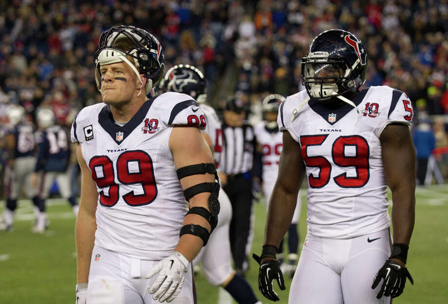 Texans defensive end J.J. Watt (99) and outside linebacker Whitney Mercilus (59) walk off the field after a New England Patriots touchdown during the fourth quarter. Photo: Brett Coomer, Houston Chronicle / © 2013  Houston Chronicle