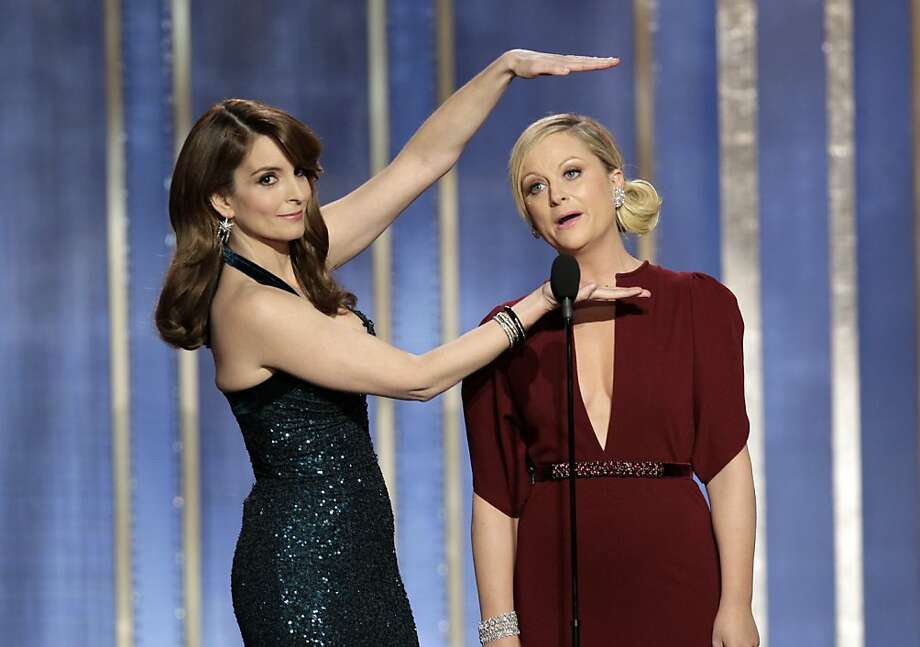 This image released by NBC shows co-hosts Tina Fey, left, and Amy Poehler on stage during the 70th Annual Golden Globe Awards held at the Beverly Hilton Hotel on Sunday, Jan. 13, 2013, in Beverly Hills, Calif. (AP Photo/NBC, Paul Drinkwater) Photo: Paul Drinkwater, Associated Press
