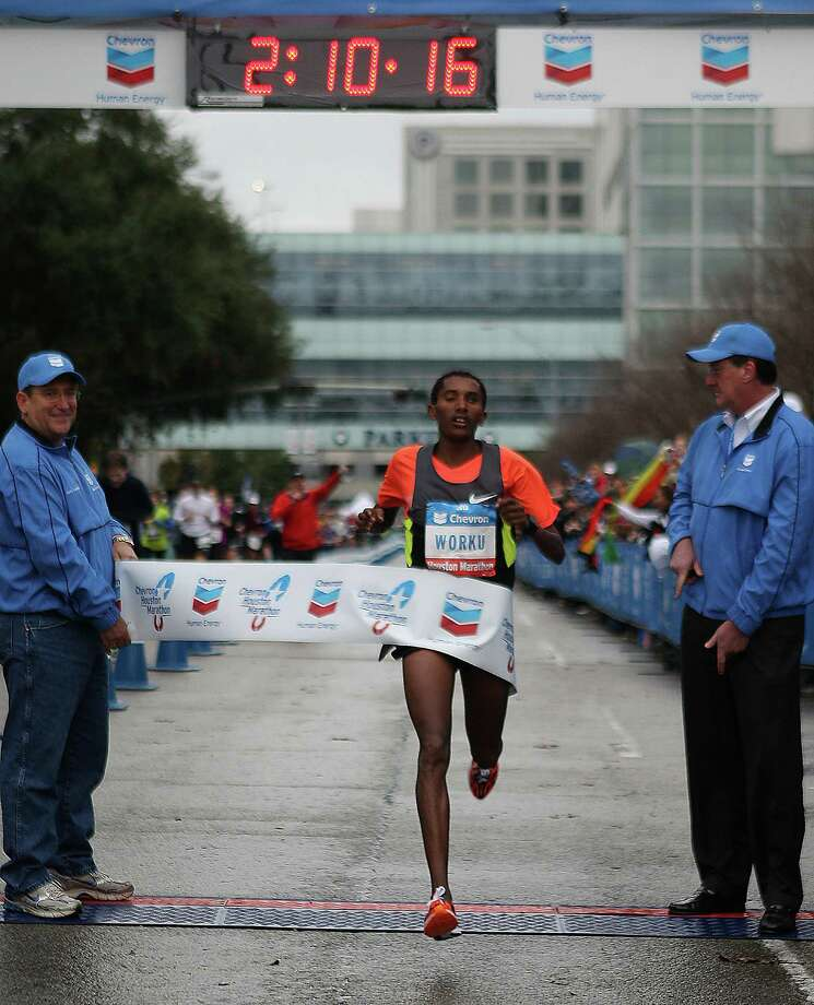 Ethiopia's Bazu Worku, left, and Merima Mohammed break the tape to win their respective divisions of the Chevron Houston Marathon on Sunday. Worku captured the men's title in 2 hours, 10 minutes, 17 seconds, while Mohammed coasted to victory in the women's race with a time of 2:23:37. Photo: James Nielsen, Staff / © Houston Chronicle 2013