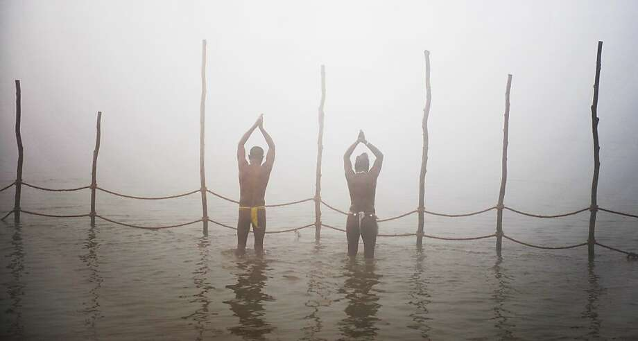 Devotees pray while taking a dip at the Sangham or confluence of the Yamuna and Ganges river at day break at the Kumbh Mela celebration in Allahabad on January 13, 2013.  The Kumbh Mela in northern India, starting January 13 and stretching over 55 days, attracts ash-covered holy men who run into the frigid waters, a smattering of international celebrities, as well as millions upon millions of ordinary Indians to Allahabad, at the confluence of the rivers Yamuna and Ganges. Photo: Roberto Schmidt, AFP/Getty Images