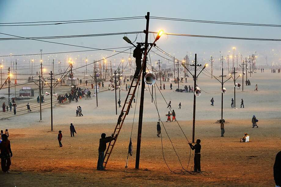 Workers fix a lightpost, one of many that will illuminate the vast grounds receiving the millions of Hindu devotees that will congregate here for the next couple of months to celebrate the Kumbh Mela, in Allahabad on January 13, 2013. Worshippers, believe a dip in the holy waters cleanses them of their sins. The Kumbh Mela in northern India, starting on January 14 and stretching over 55 days, attracts ash-covered holy men who run into the frigid waters, a smattering of international celebrities, as well as millions upon millions of ordinary Indians to Allahabad. Photo: Roberto Schmidt, AFP/Getty Images