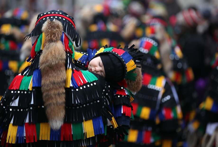 A child sleeps on his father's shoulder during the fools  parade in Elzach, Germany, Sunday Jan. 13,  2013. Every three to four years, the  'fools' of that region parade  in traditional costumes. Photo: Marc Eich, Associated Press