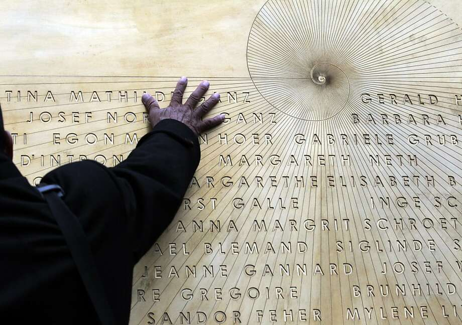 A relative of the Costa Concordia shipwreck's victims touches a commemorative plaque bearing the names of the 32 people who lost their lives in the disaster, in the Tuscan island Isola del Giglio, Italy, Sunday, Jan. 13, 2013. Survivors of the Costa Concordia shipwreck and relatives of the 32 people who died marked the first anniversary of the grounding Sunday. The first event of Sunday's daylong commemoration was the return to the sea of part of the massive rock that tore into the hull of the 112,000-ton ocean liner on Jan. 13, 2012 and remained embedded as the vessel capsized along with its 4,200 passengers and crew. Photo: Gregorio Borgia, Associated Press