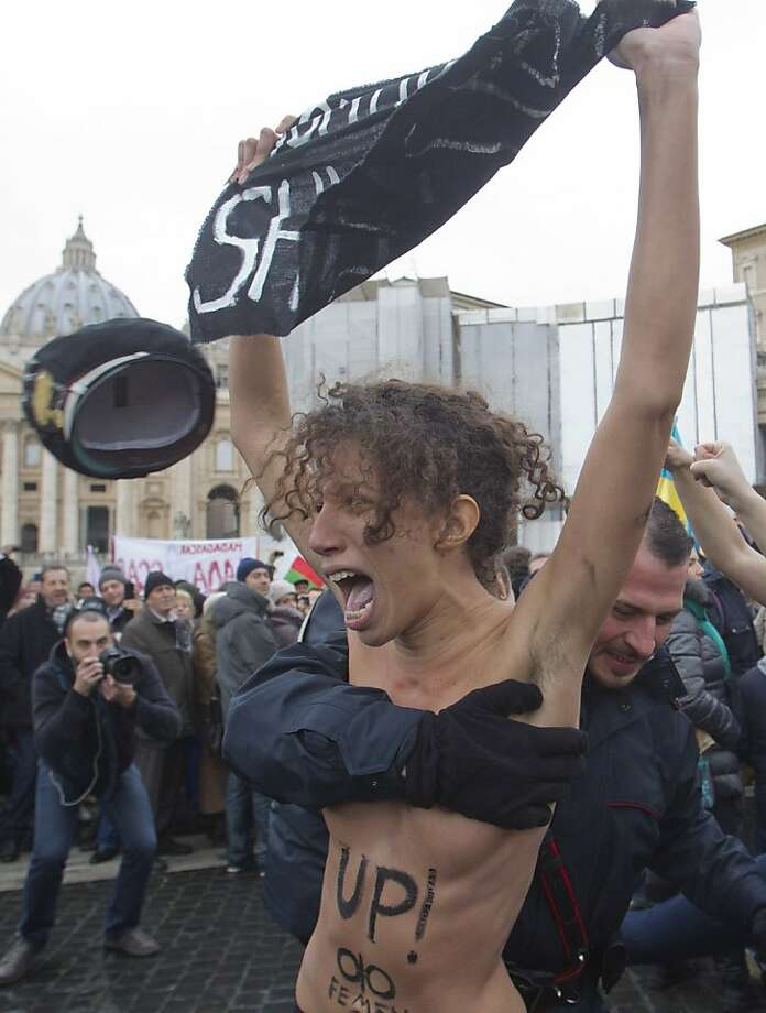 "The hat-less rounds up the topless: An Italian police officer loses his lid as he strong-arms a gay-rights demonstrator into custody after she and three other women stripped off their tops in St. Peter's Square at the Vatican. The women, who had the slogans ""In Gay We Trust"" and ""Shut Up"" painted on their backs, were protesting the Vatican's opposition to same-sex marriage. The commotion did not appear to disturb the pope, who delivered his traditional prayer. Photo: Angelo Carconi, Associated Press"