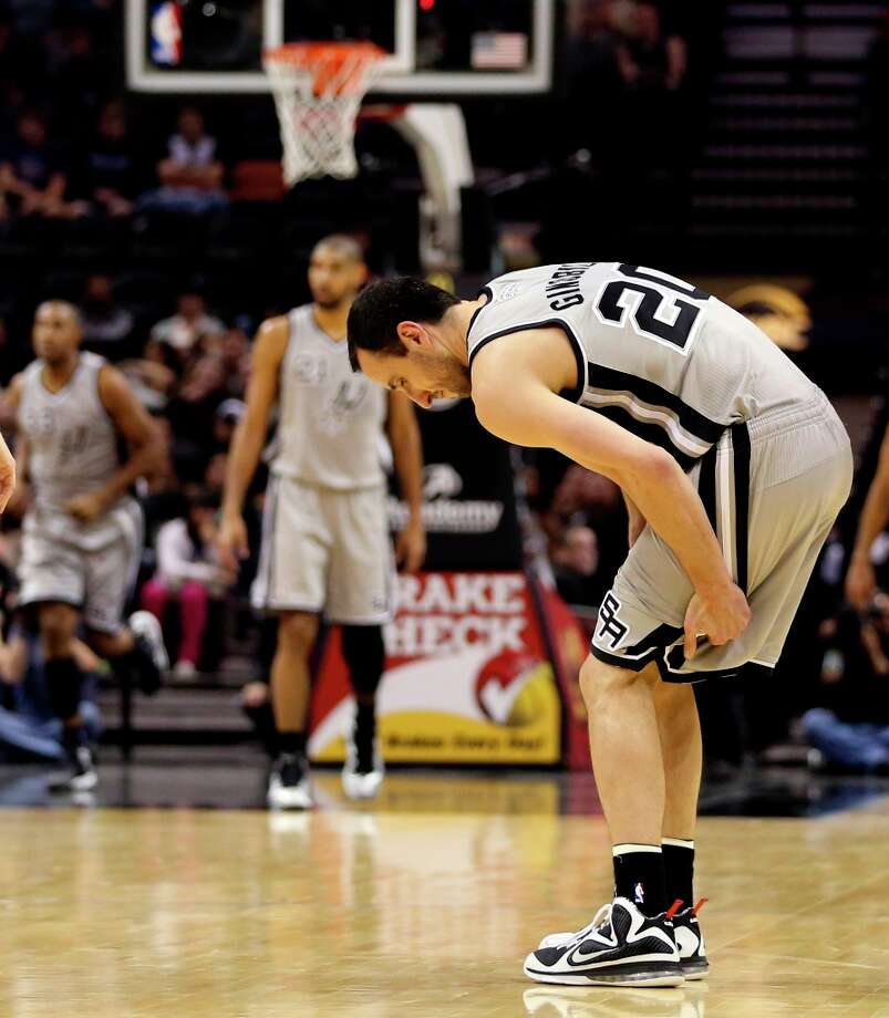 The Spurs' Manu Ginobili holds his left leg during a play against the Minnesota Timberwolves in the first half at the AT&T Center, Sunday, Jan. 13, 2013. Ginobili left the game soon after. Photo: Jerry Lara, San Antonio Express-News / © 2013 San Antonio Express-News