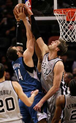 The Spurs' Tiago Splitter attempts to block a shot by Minnesota Timberwolves' Nikola Pekovic in the first half at the AT&T Center, Sunday, Jan. 13, 2013. Photo: Jerry Lara, San Antonio Express-News / © 2013 San Antonio Express-News