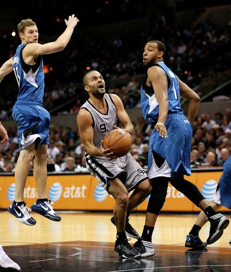 The Spurs' Tony Parker drives through the defense of Minnesota Timberwolves' Luke Ridnour, left, and Derrick Williams in the second half at the AT&T Center, Sunday, Jan. 13, 2013. The Spurs won 106-88. Photo: Jerry Lara, San Antonio Express-News / © 2013 San Antonio Express-News