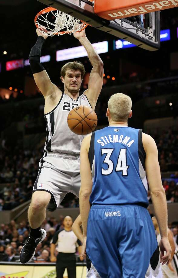 The Spurs' Tiago Splitter dunks the ball as Minnesota Timberwolves' Greg Stiemsma looks on in the second half at the AT&T Center, Sunday, Jan. 13, 2013. The Spurs won 106-88. Photo: Jerry Lara, San Antonio Express-News / © 2013 San Antonio Express-News