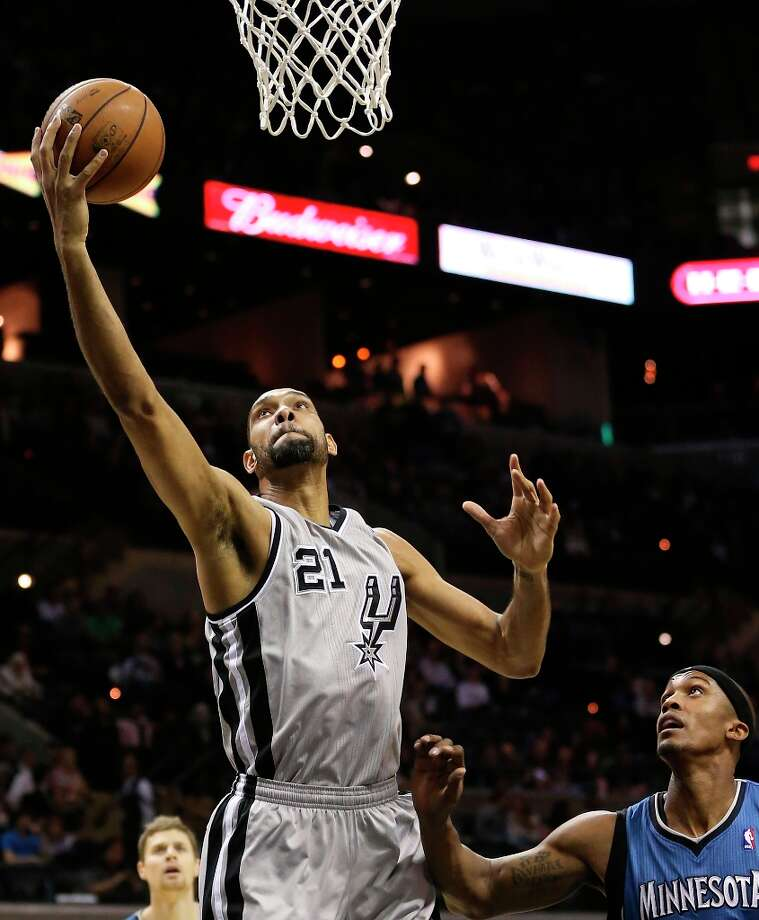 The Spurs' Tim Duncan goes for two over Minnesota Timberwolves' Dante Cunningham in the first half at the AT&T Center, Sunday, Jan. 13, 2013. Photo: Jerry Lara, San Antonio Express-News / © 2013 San Antonio Express-News