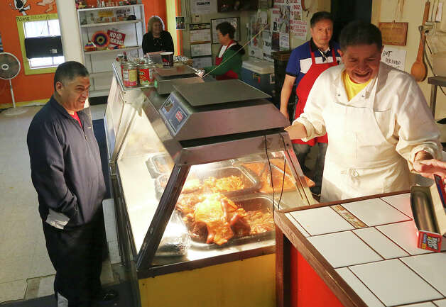 "Jose Resendiz, left, places an order of carnitas as Luis Almanza weighs the order at Carnitas Uruapan at 2530 Ruiz Street, Sunday, Jan. 13, 2013. Almanza is the owner and is also a longtime friend of legendary conjunto accordionist and National Endowment for the Arts Heritage Fellowship recipient Santiago Jimenez, Jr. Every Sunday morning for the last year or so, Jimenez and bajo sexto musician Margarito Guajardo have performed under the radar on Sunday mornings at the West Side restaurant. ""To me, he is San Antonio music,"" Almanza said, ""I knew the father, I know the brothers. Like they are to music, we are to carnitas."" Almanza has been in the carnitas business for 65 years. Photo: Jerry Lara, San Antonio Express-News / © 2013 San Antonio Express-News"