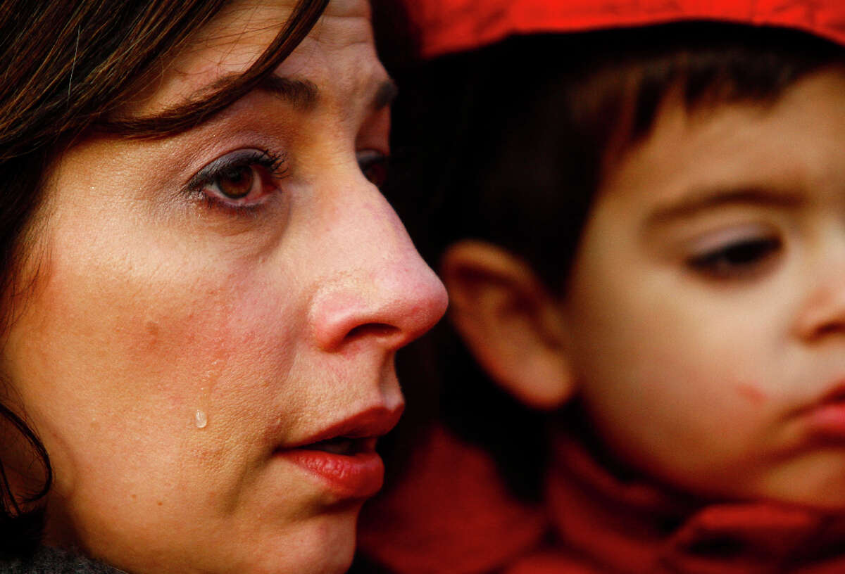 A tear rolls down the cheek of Sharon Perez as she holds her son Rowan, 3, at the StandUp Washington March and Rally for Gun Control on Sunday, January 13, 2013 in Seattle. Marchers called for sensible gun control laws in the wake of the tragic shooting at Sandy Hook Elementary School in Connecticut.