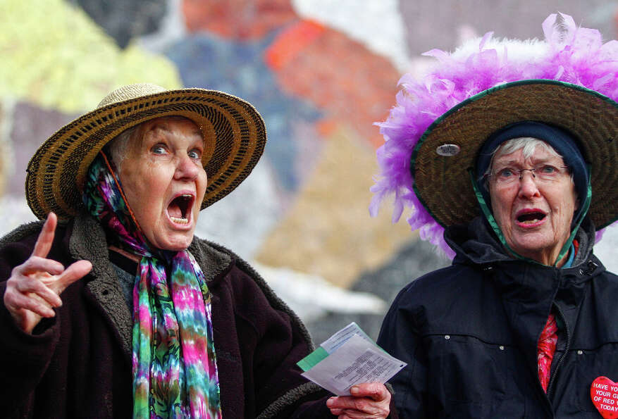 Raging Grannies Carolyn Hale, left, and Nina Murano sing Read our lips! No more guns, during the Sta
